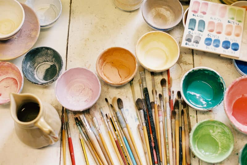 brushes and paintbowls on a desktop