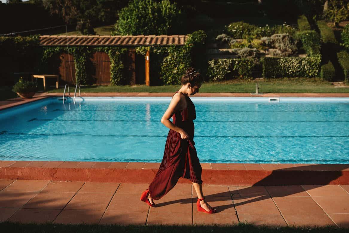 bridesmaid walking by the pool at villa di ulignano wedding