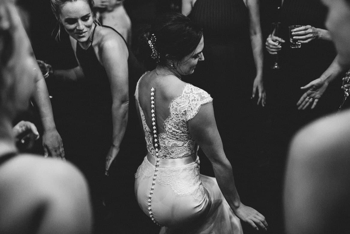 bride in a lace wedding dress dancing with bridesmaids at villa di ulignano wedding