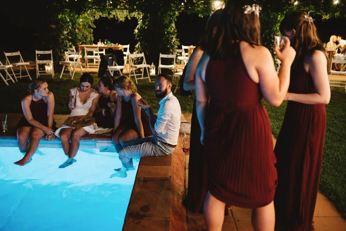 bride and bridesmaids eating pizza by the pool in the evening during wedding at villa di ulignano