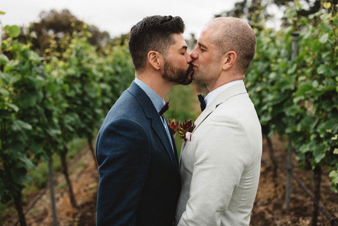 Tasmania wedding photographer portrait of groom and groom kissing