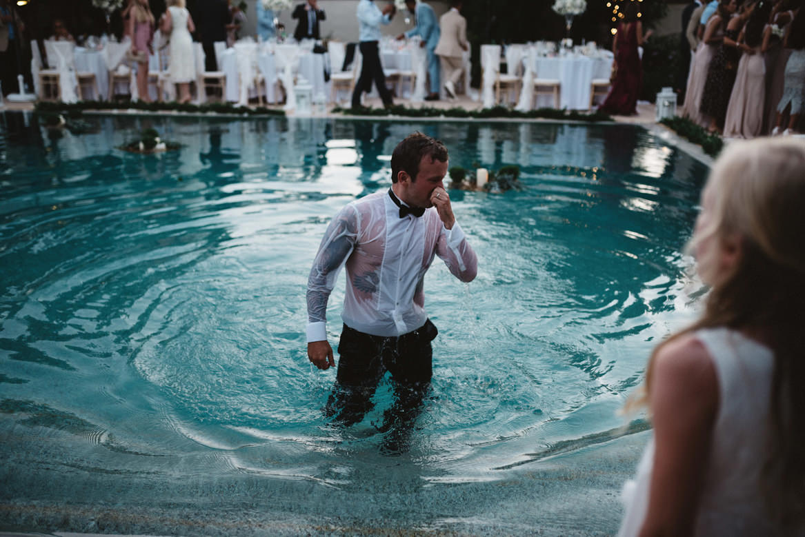 tattooed groom getting out of pool at casa rupi wedding