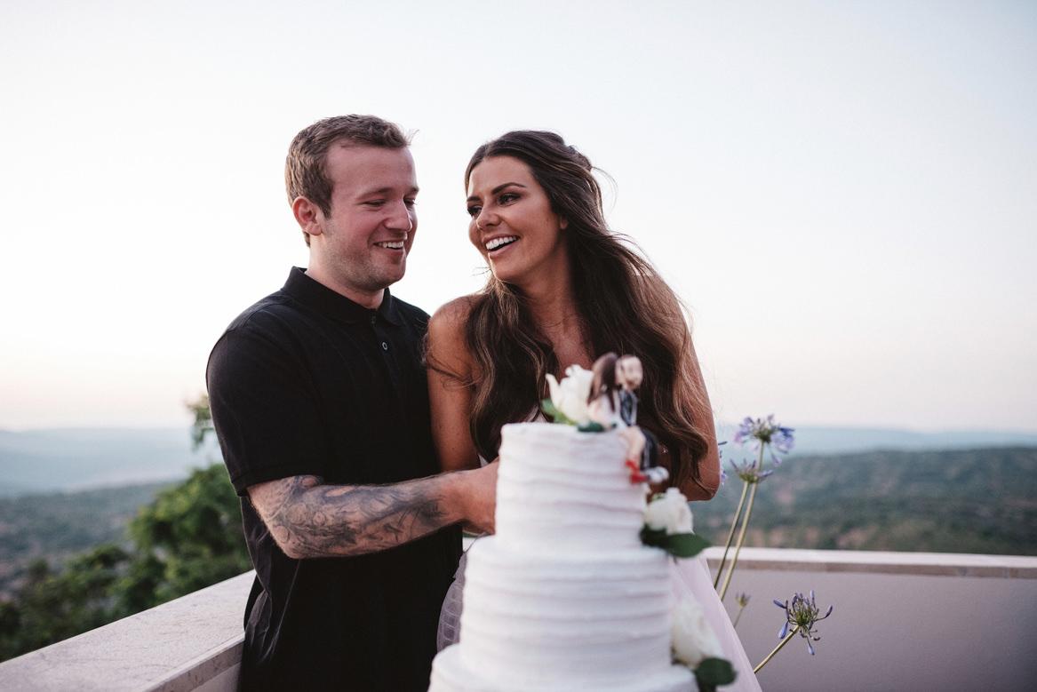 bride and tattooed groom cutting cake in balcony during casa rupi wedding