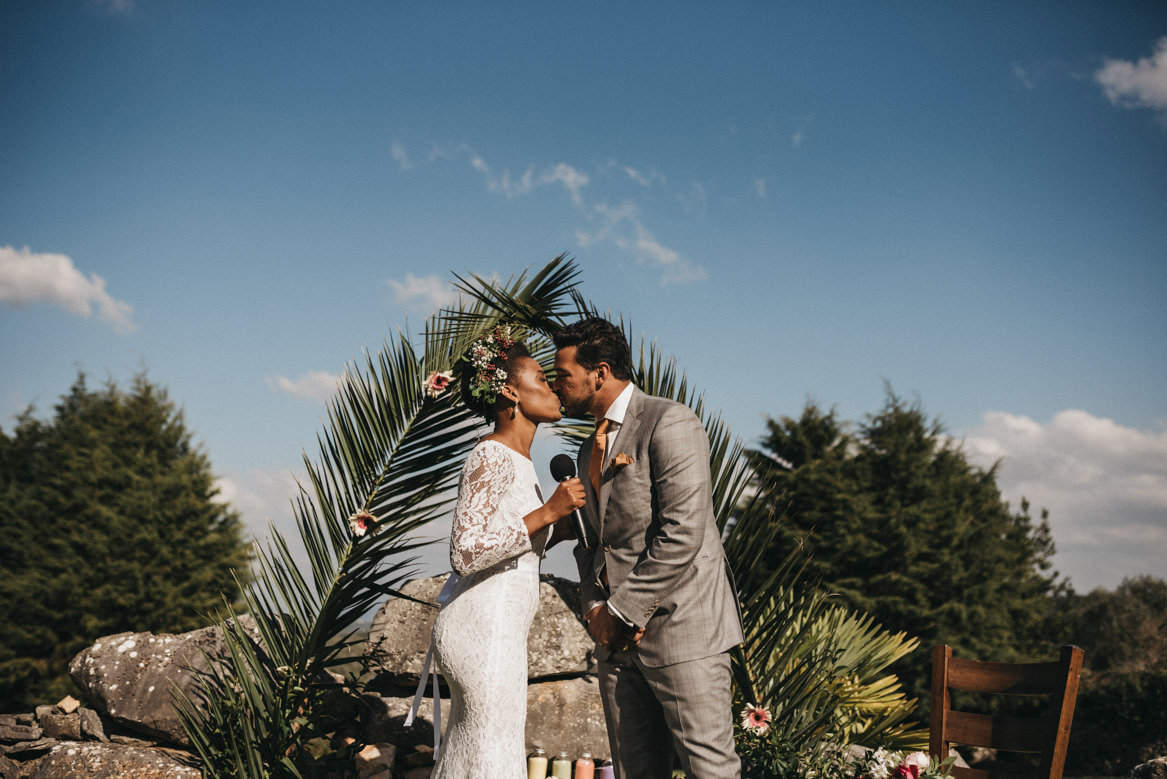 Bride and groom kiss in outdoor ceremony