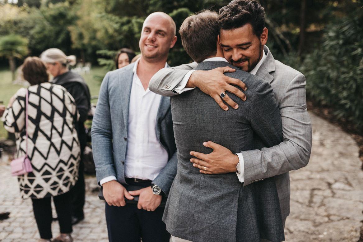 Groom hugging friends after ceremony