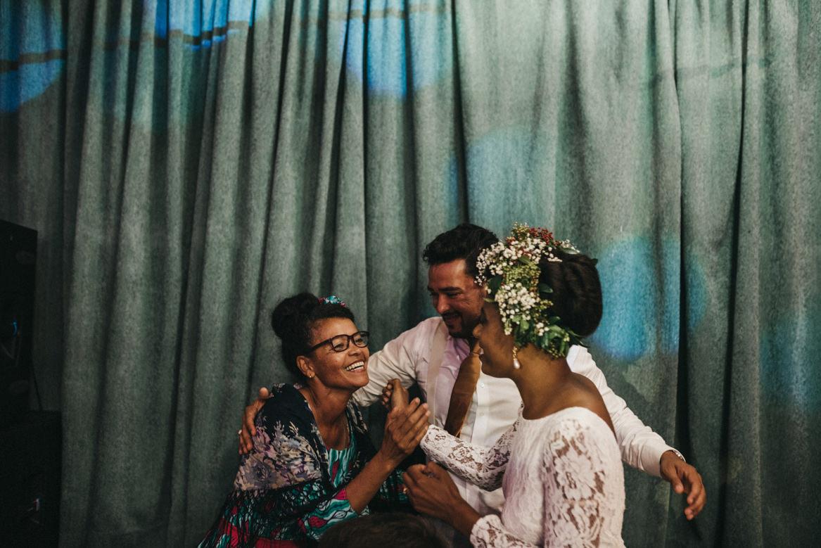 Bride and groom hugging mother